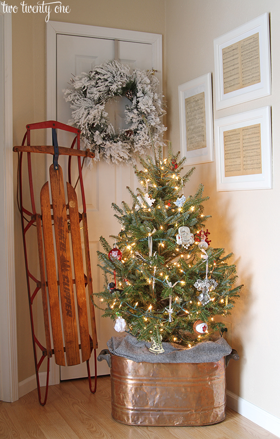 christmas entryway with copper boiler tree stand vintage sled and framed vintage christmas sheet