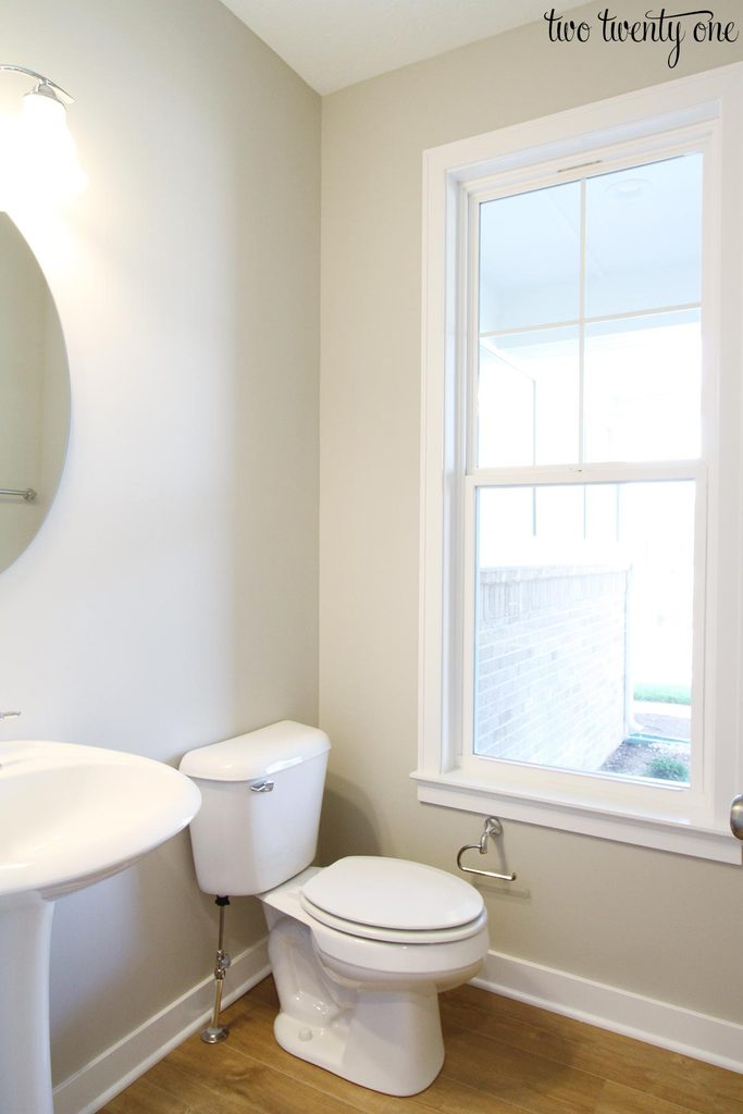 half bathroom with toilet, sink, and window
