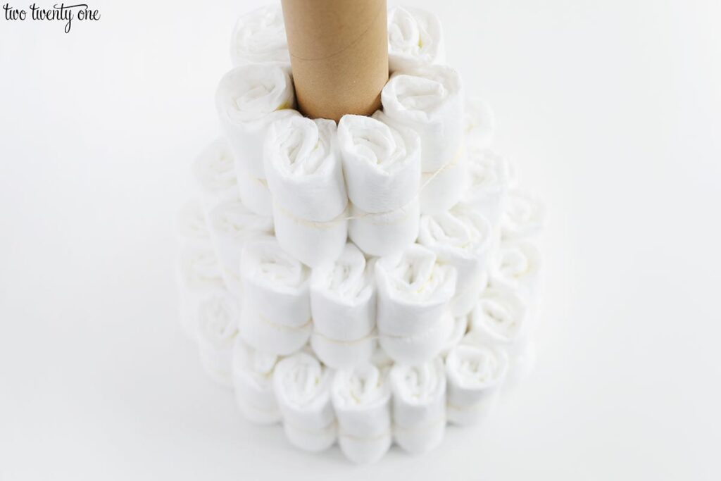three tiers of rolled up diapers circling a cardboard tube