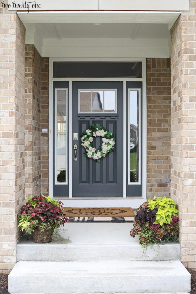 front porch with dark gray door and foliage planters