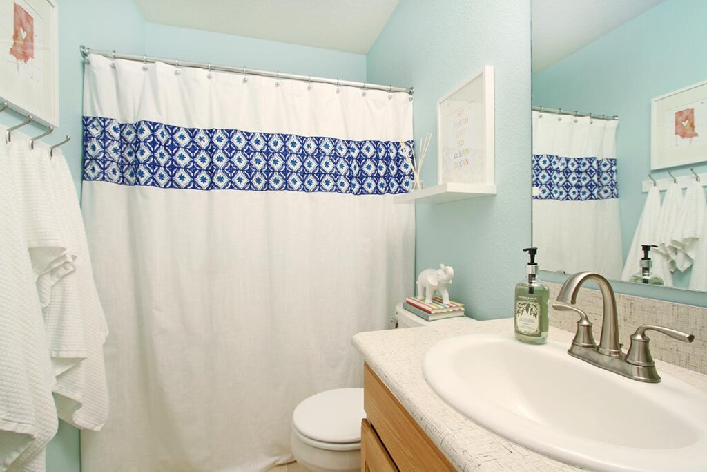Sherwin Williams Tidewater in guest bathroom with white shower curtain