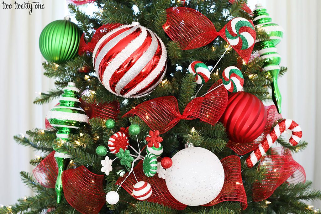 artificial christmas tree with red white and green ornaments, red mesh ribbon and red, white and green picks