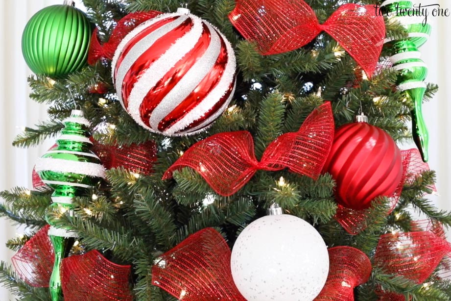 different size red white and green ornaments with red mesh ribbon