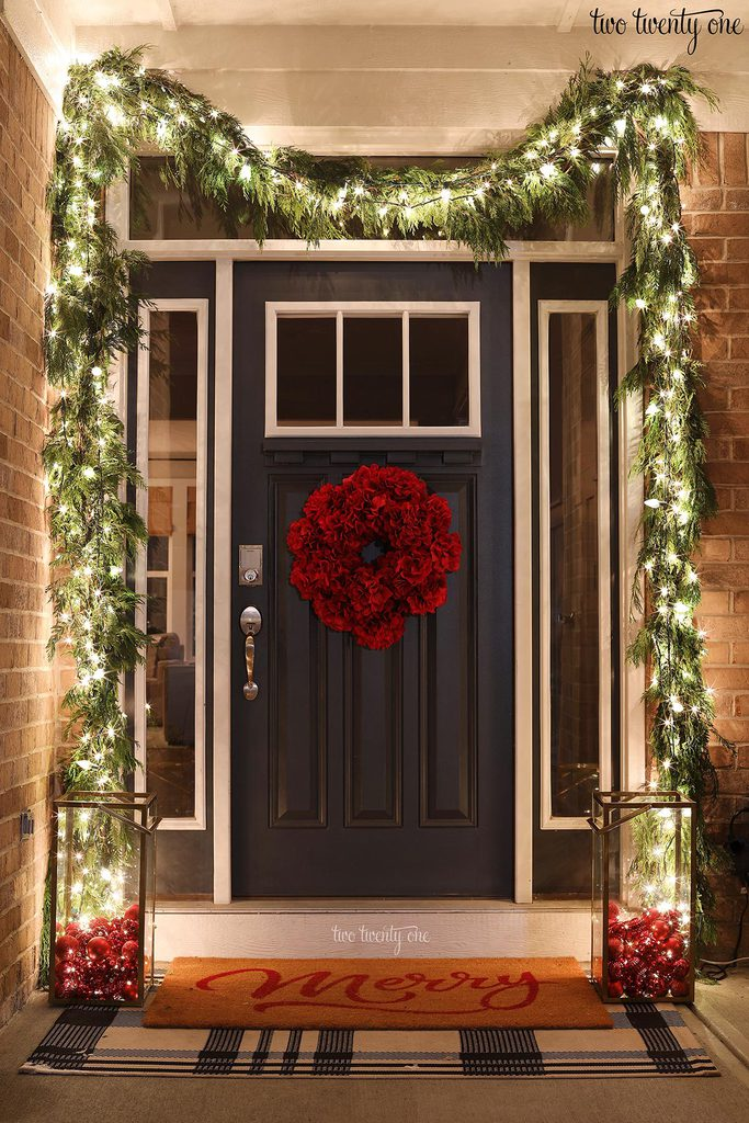 front door decorated for Christmas with cedar garland and lights