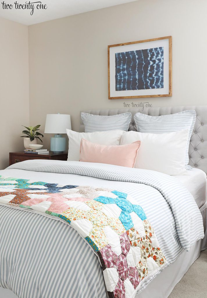 bed with vintage quilt, blue and white striped duvet, blue striped euro shams, white pillows, and light pink pillow. Shibori wall art above the bed.