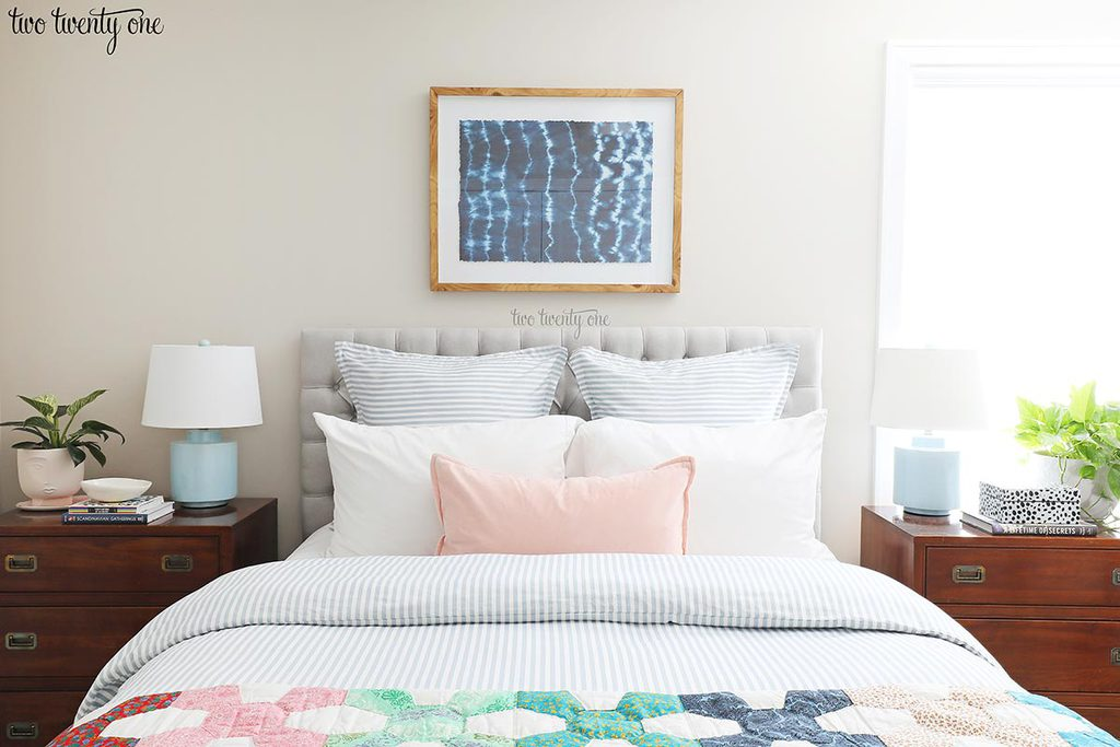 1986 Ethan Allen campaign-style nightstands, topped with blue lamps, plants, and books. The nightstands flank a queen size bed, bed with gray tufted headboard, pillows, blue and white striped duvet and vintage quilt. Shibori wall art above bed.