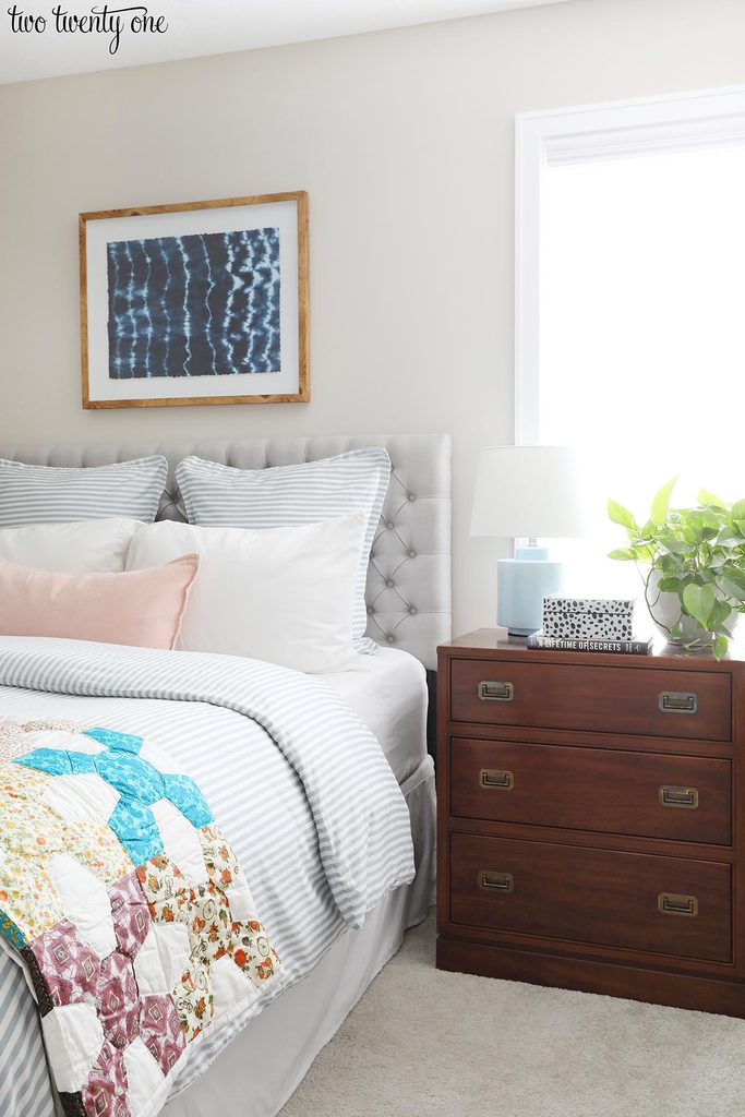 1986 Ethan Allen campaign-style night stand, bed with gray tufted headboard, pillows, blue and white striped duvet and vintage quilt. Shibori wall art above bed.