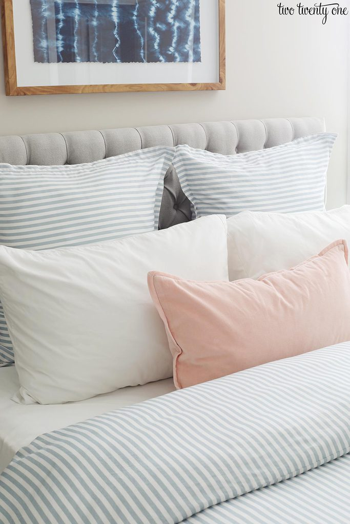 blue striped duvet cover with blue striped euro shams, white pillows, and a light pink pillow