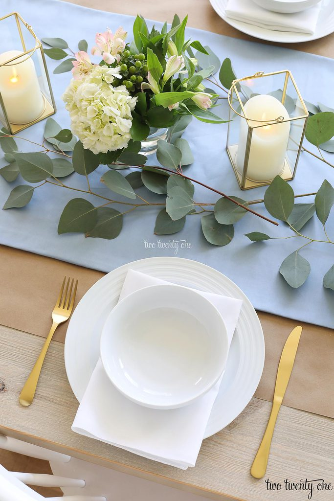table set with blue table runner off-white candles in gold trimmer lanterns and flower arrangements of hydrangeas and greenery, white plate topped with a white napkin and white bowl with gold fork and knife
