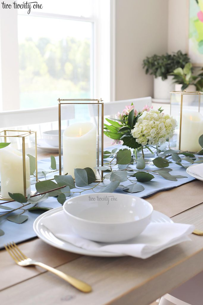 table set with blue table runner off-white candles in gold trimmer lanterns and flower arrangements of hydrangeas and greenery and white table setting with gold utensils