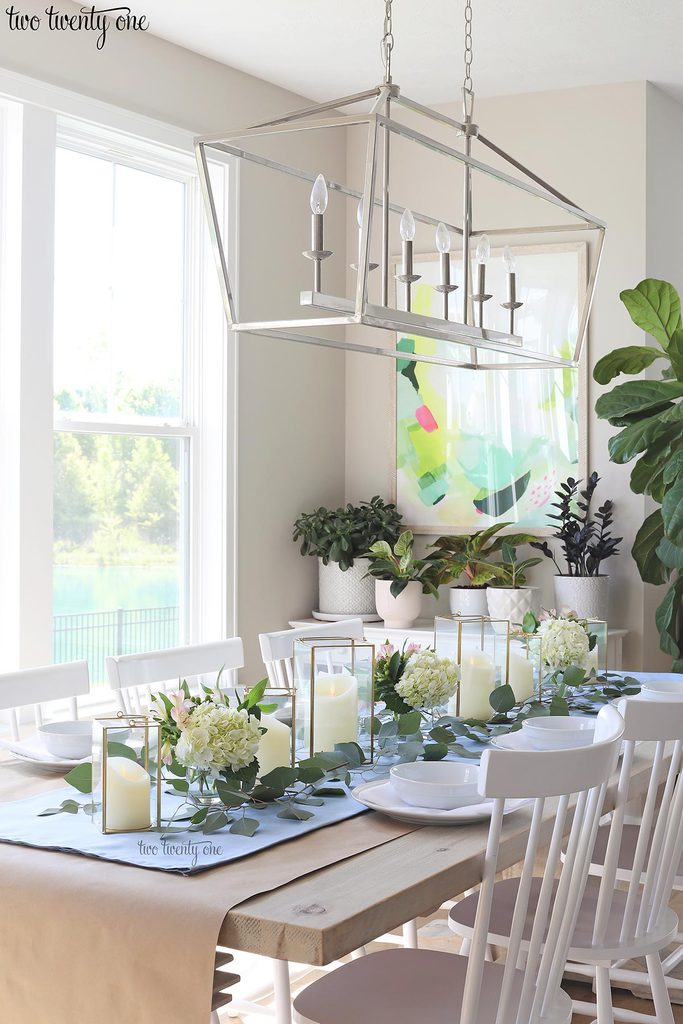 table set with blue table runner off-white candles in gold trimmer lanterns and flower arrangements of hydrangeas and greenery