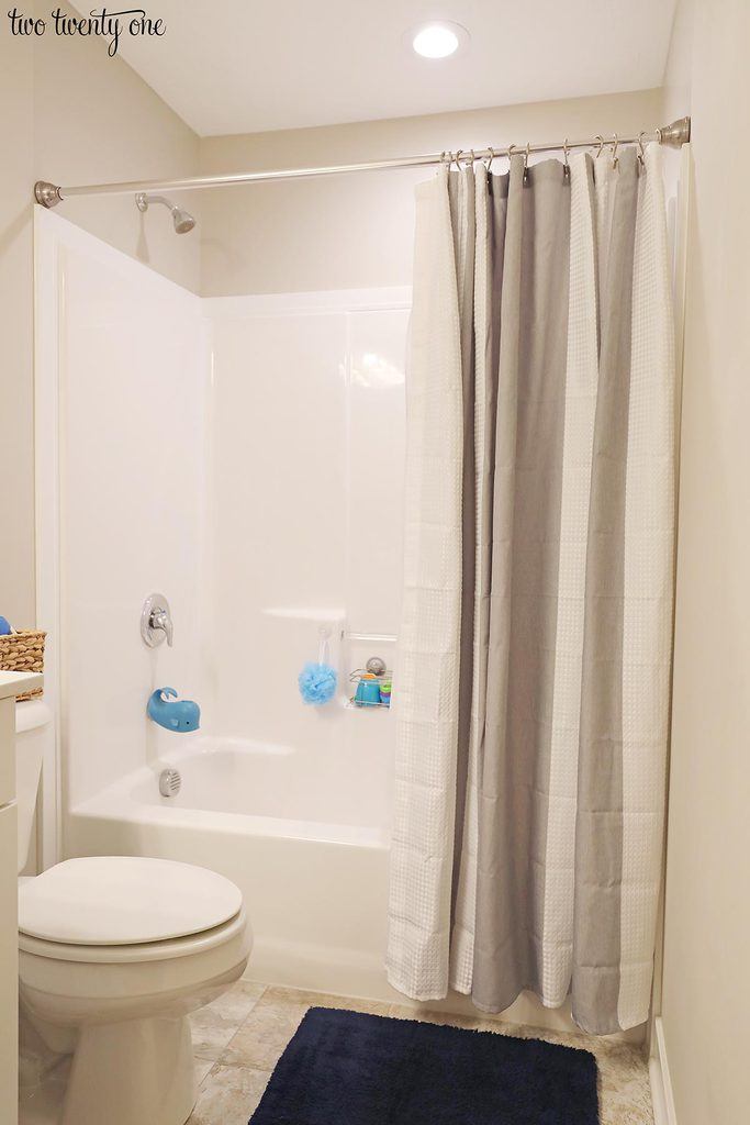 shower with gray and white shower curtain