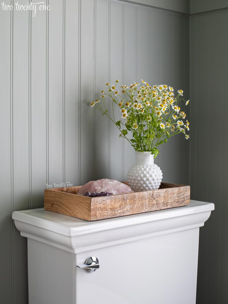 kohler memoirs toilet with wooden tray on top with chamomile flowers in white hobnail vase