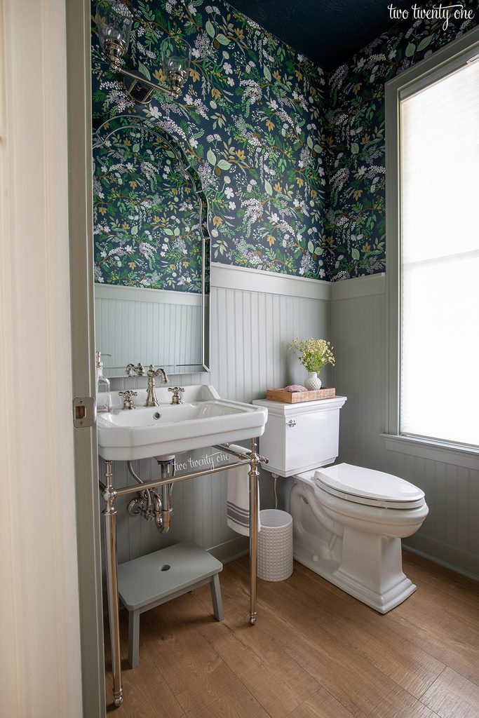 powder room with console sink, toilet, beadboard painted benjamin moore oil cloth on the bottom, rifle paper co juniper forest wallpaper on top