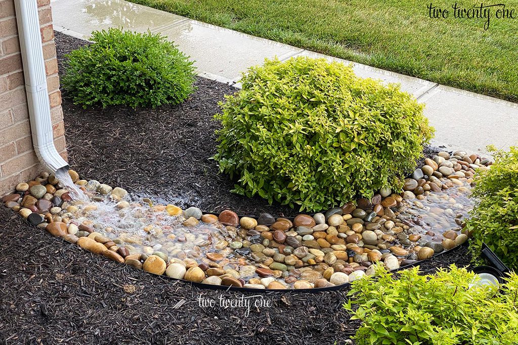 dry creek bed with rain water from downspout