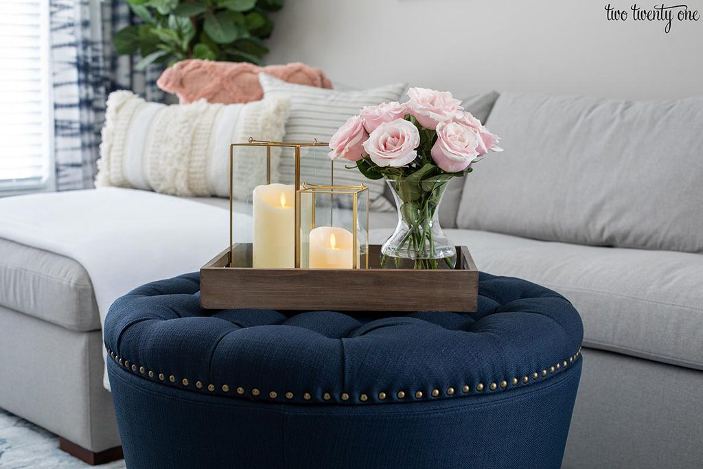 navy ottoman with tray on top. Tray has two lanterns with candles in them and a vase filled with pink roses