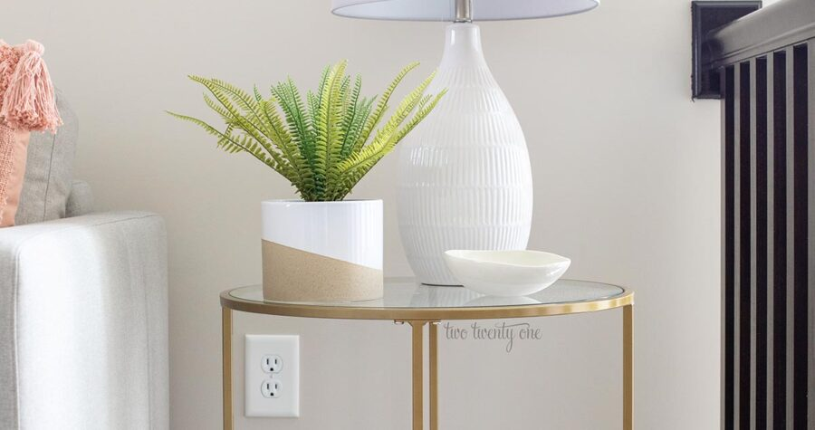 gold side table with glass top. fake plant and white lamp with gray shade on top