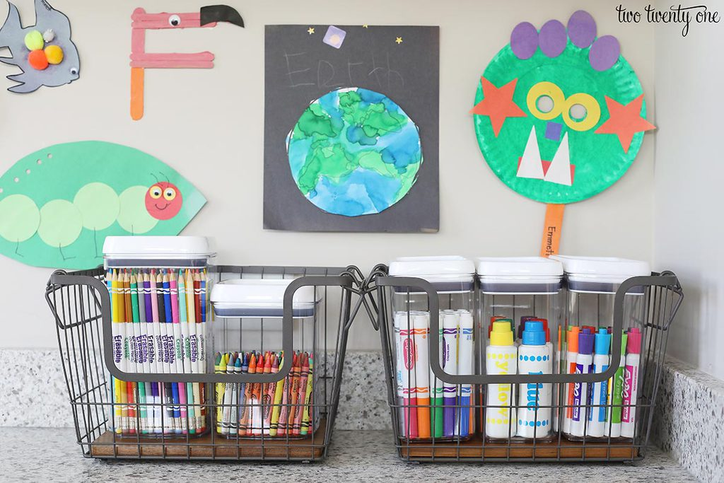 Markers, crayons, colored pencils in clear storage containers. The containers are inside wire and wood baskets.